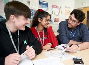 一个水平的学生在老师的帮助下在课桌上工作