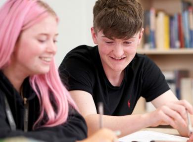两个学生微笑着看课本