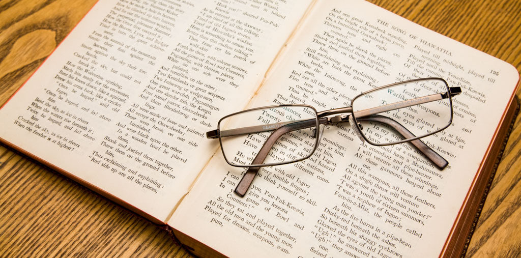A pair of reading glasses resting on a book of Longfellow poems