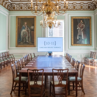 Boardroom layout with in-built av facilities in a grand room with large portraits