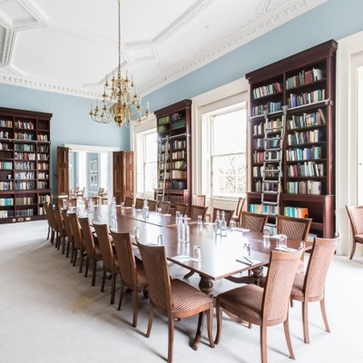 A long boardroom meeting table in an inspiring room with floor to ceiling bookshelves, big windows and golden chandeliers