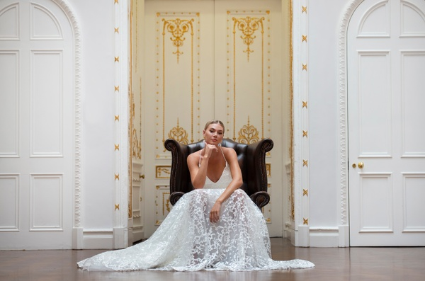 Woman in wedding dress sitting in arm chair at photoshoot venue in London