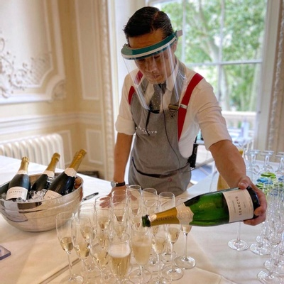 A waiter serving champagne in a white room whilst wearing a clear face protector