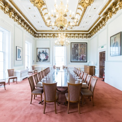 Long boardroom meeting table in grand room with high ceilings and chandeliers