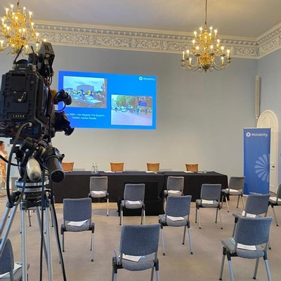 A large room with socially distanced conference chairs, a top table and a presentation projected onto the wall.