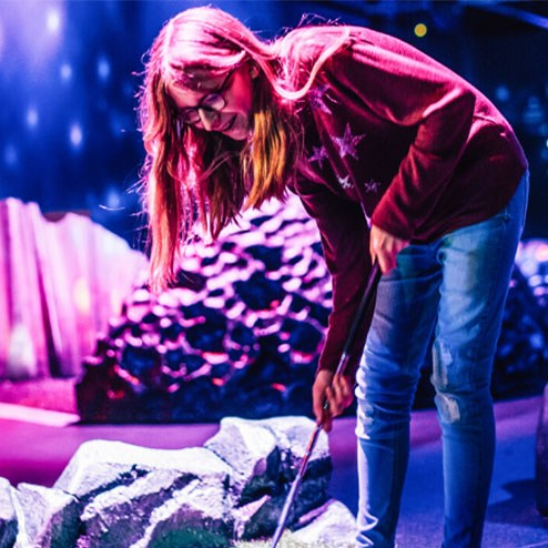 Girl Playing Mini Golf at Airtastic Space themed Adventure Golf