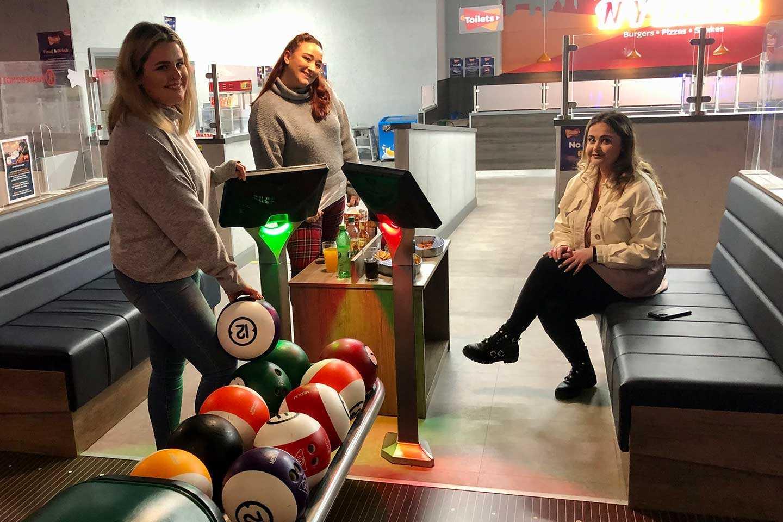 3 women sitting by an Airtastic Bowling Lane