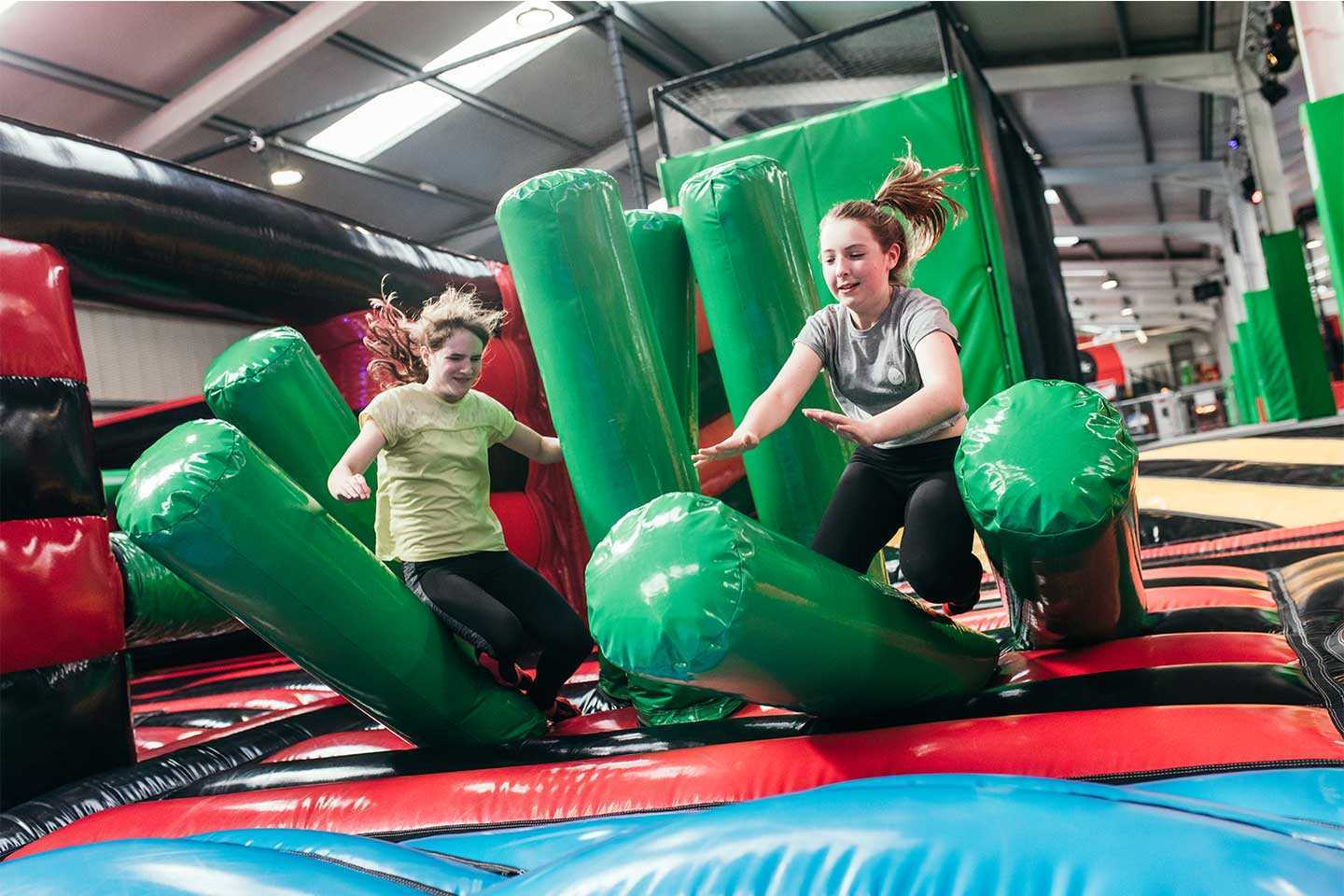 Girl and Boy going through inflatable obstacles