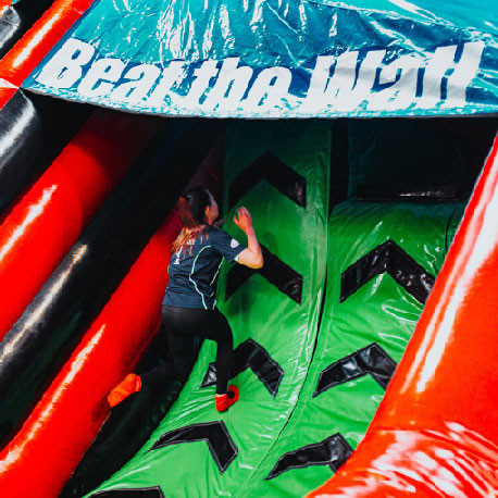Girl trying to climb Airtastic Inflata Beat the Wal
