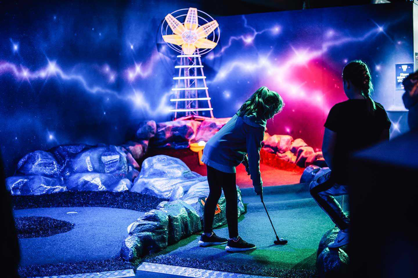 2 Girls playing Mini Golf at Airtastic Space Themed Course