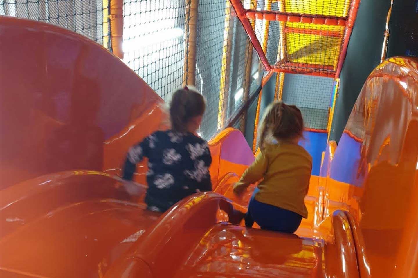 two kids going down wavy slide at Airtastic Soft Play