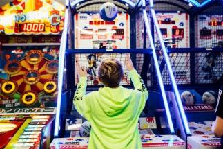 Girl Throwing a Basket Ball into a Hoop At Airtastic Amusement Arcade