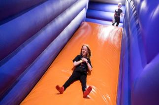 Little Girl Sliding down big orange slide at Airtastic Inflata Park in Newtownabbey