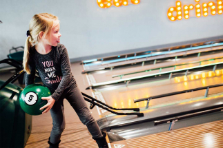 Little girl throwing ball at bowling alley