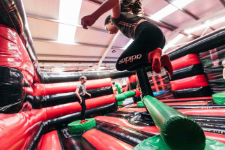 Kids jumping over the Wipe out Arm at Airtastic Inflata