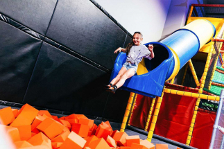 Girl sliding out of Airtastic drop slide