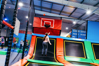 girl playing in trampoline basketball court
