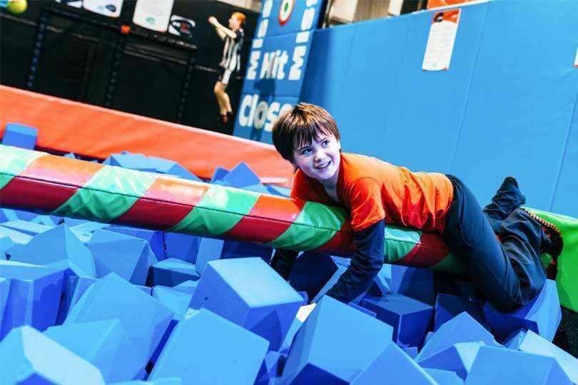 Boy Clinging to Balance Beam at Airtastic Inflata and Ninja Park