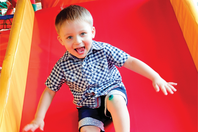 little boy smiling going down slide at Airtastic Soft Play