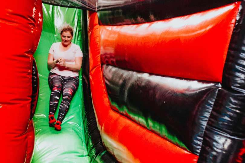 Women sliding down Airtastic Inflata Slide