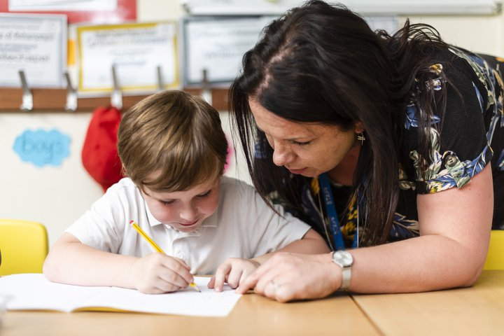 Randal Cremer_child at desk studying with teacher1