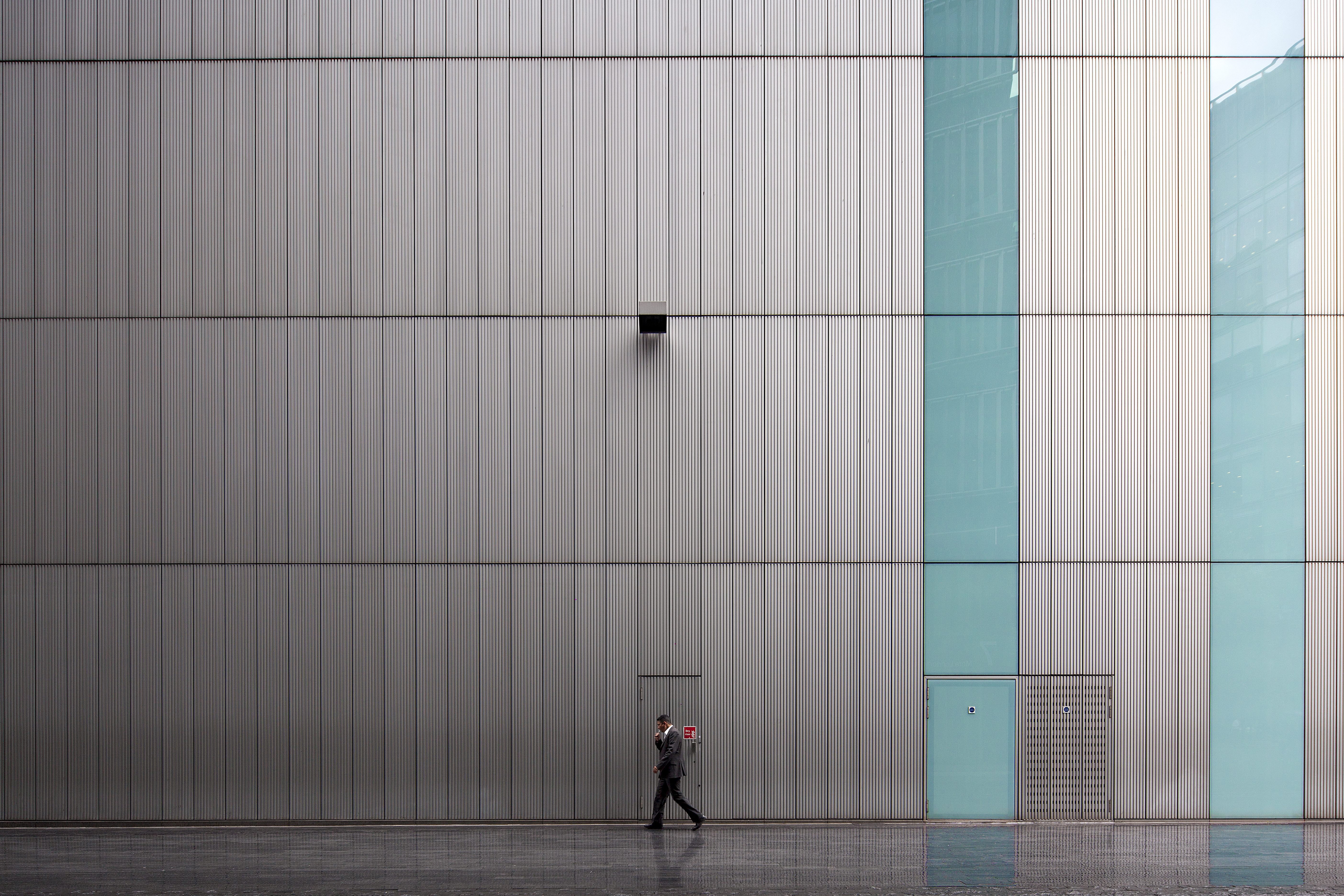 a lunch time shot in the rain of a buisness man walking in front of a large office building