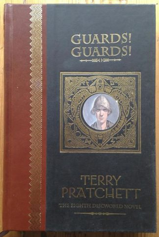 The book cover ofGuards! Guards! by Terry Pratchett. In hardcover brown, black and gold.