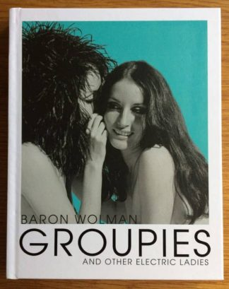 The photography book cover of Groupies and Other Electric Ladies by Baron Wolman. In hardcover white with two women whispering to each other.