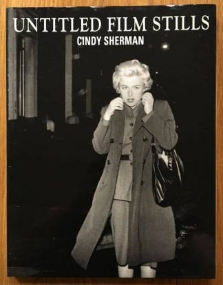 The photography book cover of Untitled Film Stills by Cindy Sherman. In dust jacketed hardcover black with Cindy Sherman.