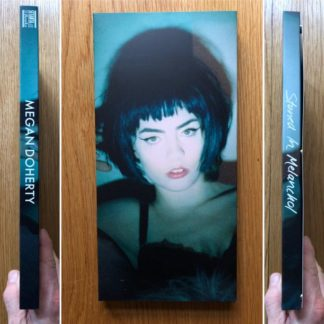 The photography book cover of Stoned in Melanchol (Cover 3) by Megan Doherty. In sofcover blue, with a young woman, wearing a black wig.