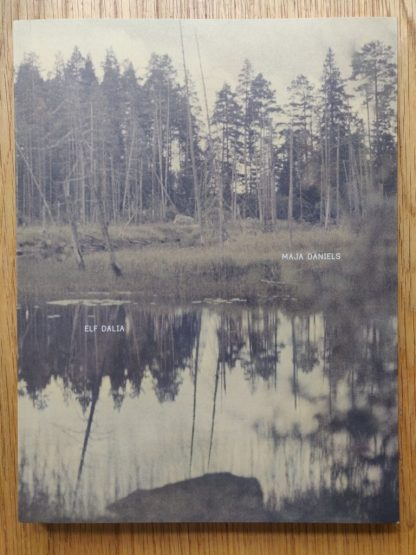 The photography book cover of Elf Dalia by Maja Daniels. In softcover brown with a forest landscape.