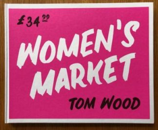 The photography book cover of Women's Market by Tom Wood. Hardback pink with white writing.