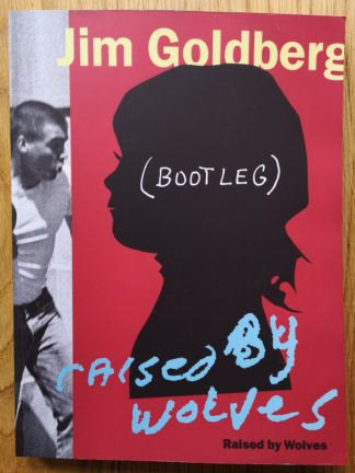 This is the cover of Raised by Wolves by Jim Goldberg with a buys head on the cover