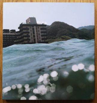 The photography book cover of Half Awake and Half Asleep in the Water by Asako Narahashi. In dust jacketed hardcover with a photograph of a building from the water.