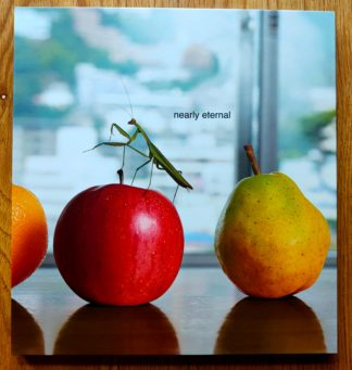 The photography book cover of Nearly Eternal by Steve Nakamura and Norbert Schoerner. In hardcover, with a pear, an apple and a mantis.