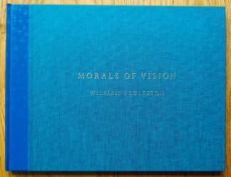 The photography book cover of Morals of Vision by William Eggleston. In hardcover blue, with the title in gold.