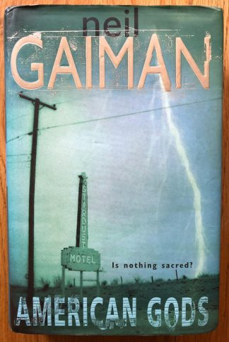 The book cover of American Gods by Neil Gaiman. In dust jacketed hardcover black.