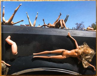 The photography book cover of Into the Fire by Matt Stuart. In hardcover with barbie dolls glue to the hood of a car.