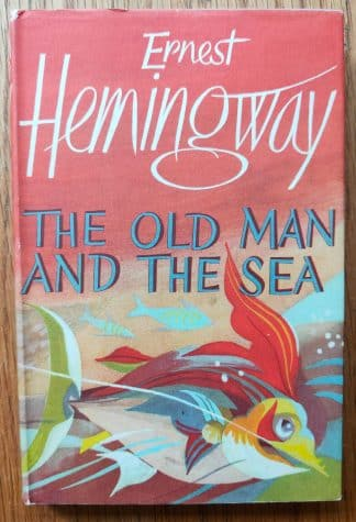 The book cover of The Old Man and the Sea by Ernest Hemingway. In dust jacketed hardcover blue.