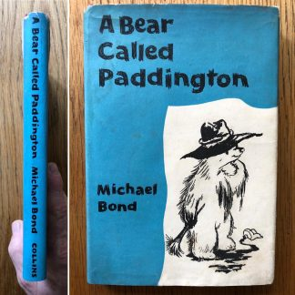 The book cover of A Bear Named Paddington by Michael Bond. In dust jacketed hardcover red.