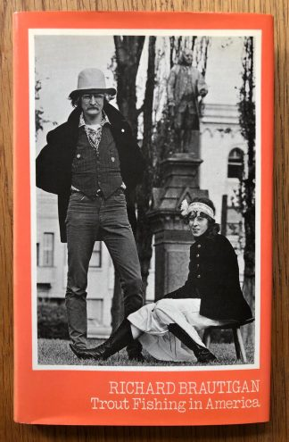 The book cover of Trout Fishing in America by Richard Brautigan. In dust jacketed hardcover grey.