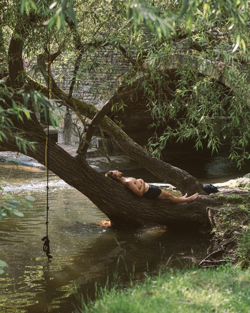 Man sunbathing on tree trunk over river