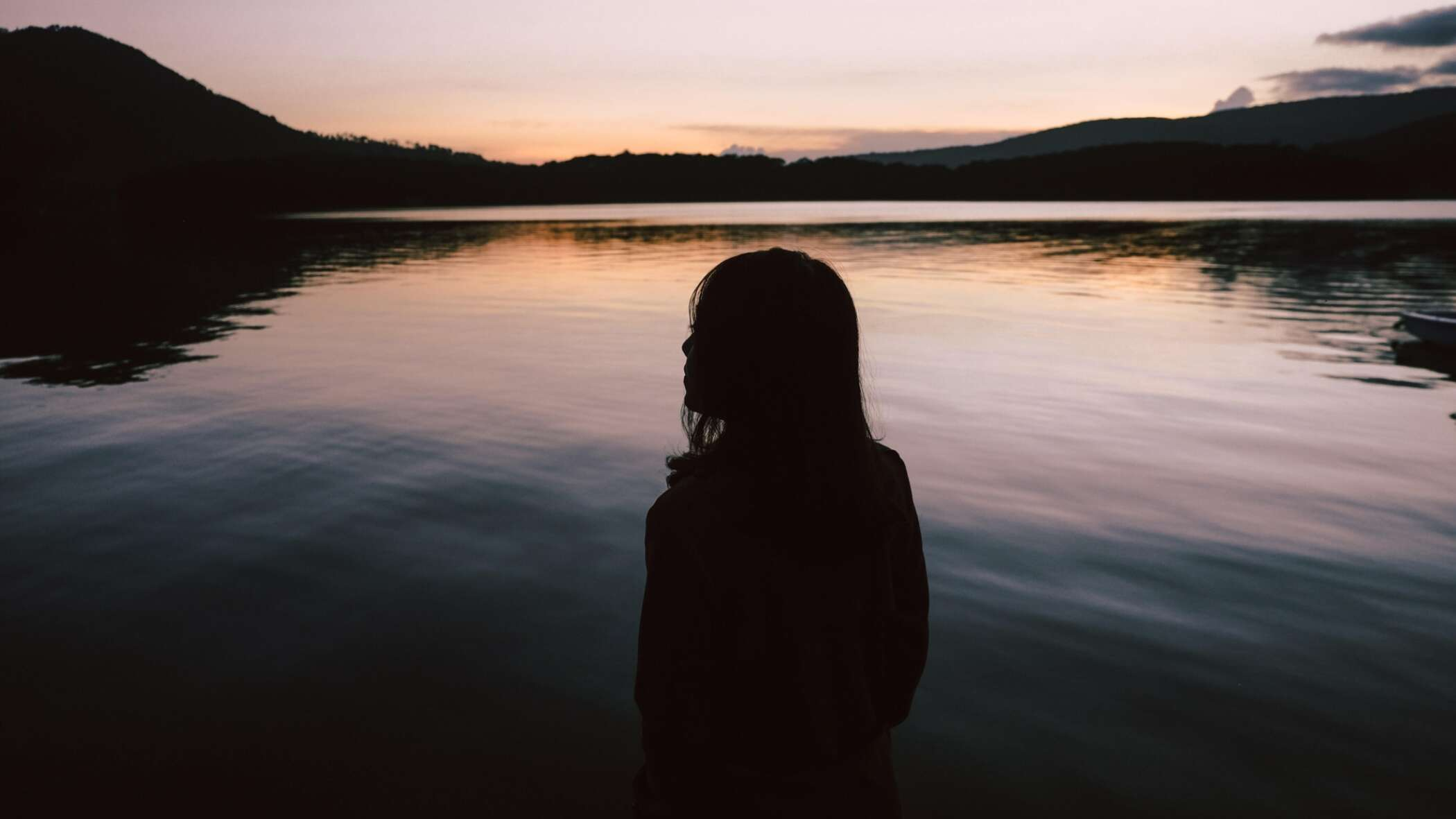 Woman silhouetted against the sunset by a river