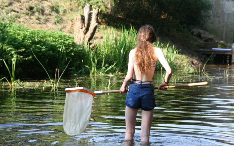 Girl with fishing net paddling in river