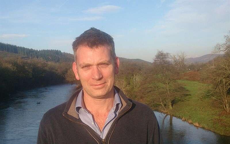 Simon Evans on a bridge over a river