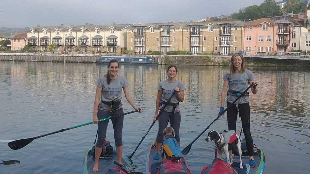 Three women and two dogs on paddleboard on the Bristol Avon