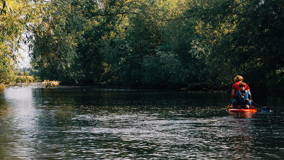 Mother and son paddle boarding a long a river
