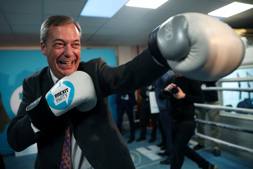 Brexit Party leader Nigel Farage wears boxing gloves during a visit at a boxing gym in Ilford, Britain, November 13, 2019. REUTERS/Hannah McKay