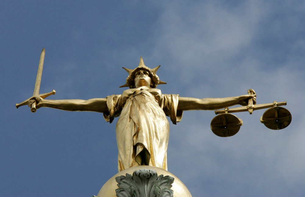 The Statue of Justice, depicted as a women with a sword in one hand and scale in her other, is seen on top of the London Central Criminal Court, the Old Bailey in London August 12, 2005. UNICS REUTERS/Russell Boyce