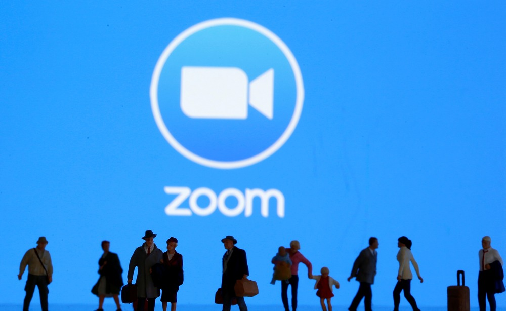Small toy figures are seen in front of displayed Zoom logo in this illustration taken March 19, 2020. REUTERS/Dado Ruvic/Illustration